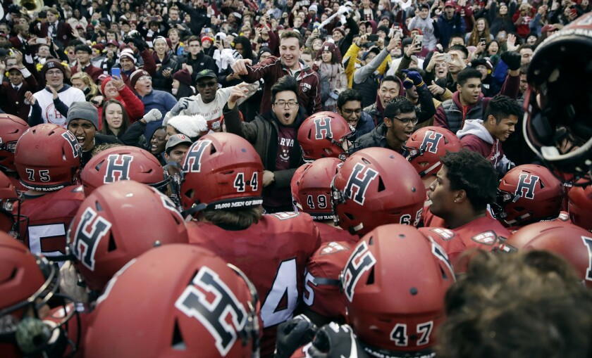 Harvard players, students and fans celebrate their 45-27 win over Yale at Fenway Park in Boston on Nov. 17, 2018.
