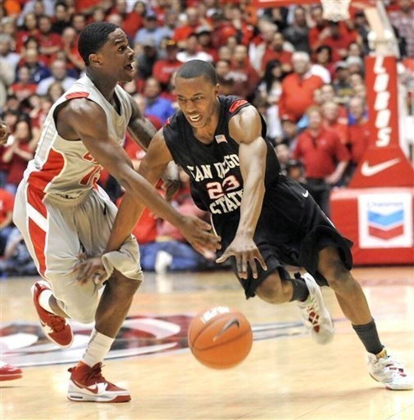 New Mexico's Jamal Fenton reaches in on San Diego State's D.J. Gay.