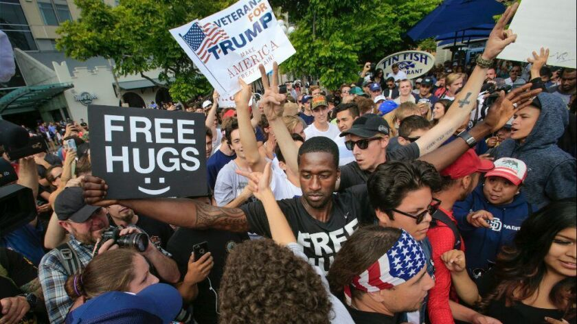 San Diegan Ken Nwadike Jr., founder of the Free Hugs Project, engages with the crowd at a Donald Trump rally in May in the Gaslamp Quarter.