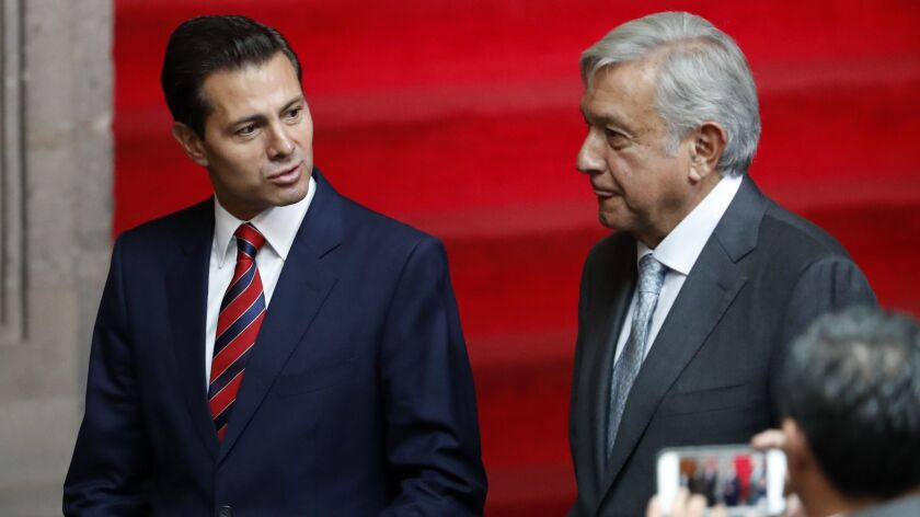 Mexican President Enrique Peña Nieto, left, and President-elect Andres Manuel Lopez Obrador talk at the National Palace in Mexico City, on Aug. 20, 2018.