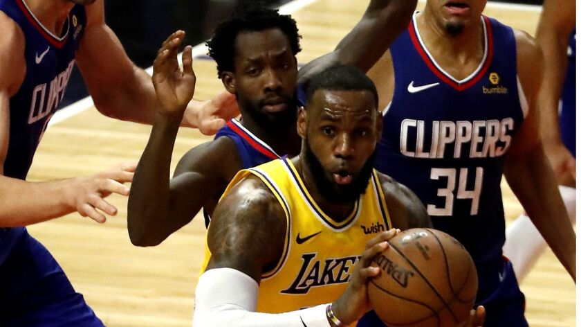 Lakers forward LeBron James looks to pass after drawing a swarm of Clippers defenders in the final minutes of the fourth quarter Thursday night.