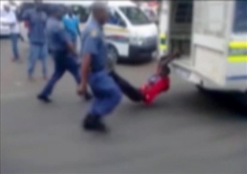 In this still frame from TV and courtesy of South African Daily Sun newspaper, showing a South African man with his hands tethered to the back of a police vehicle being dragged behind as police hold his legs up and the vehicle apparently drives off, east of Johannesburg Tuesday Feb. 26, 2013. The man died of his injuries. In video filmed on a mobile phone, uniformed police are seen trying to subdue the man, then tethering him to the back of a police vehicle which drives off, watched by a large