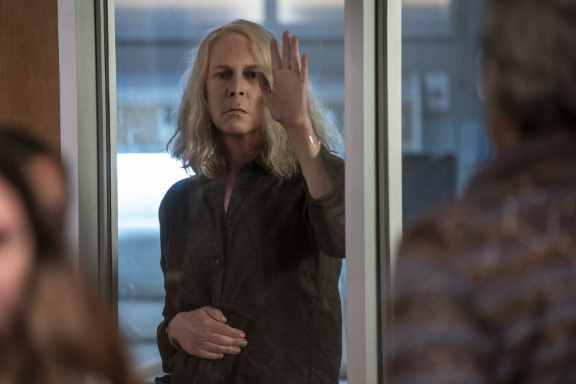 """A woman looks into a room through a glass door in the movie """"Halloween Kills."""""""