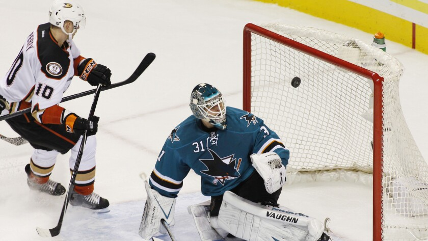San Jose Sharks goalie Antti Niemi blocks a shot in front of Anaheim forward Corey Perry during the Ducks' 6-4 loss Saturday.