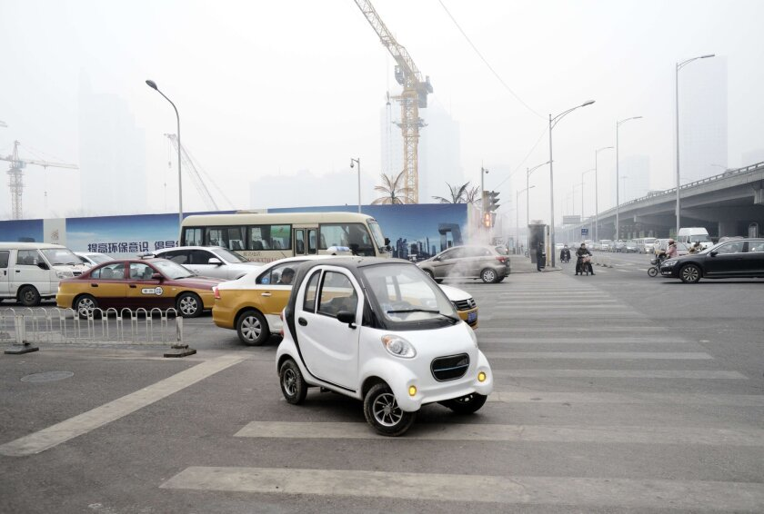 An electric car is driven through Beijing on Dec. 8, 2015.