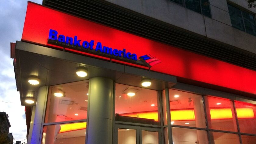 FILE- In this Nov. 6, 2017, file photo, people walk by a branch office of Bank of America in New Yor