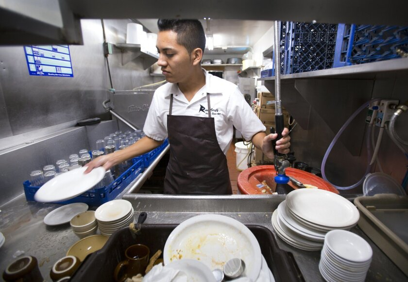 Edenils Lemus washes dishes at Rudford's Restaurant in North Park. He along with other staff  currently are paid less than  $15 per hour and will be affected by  the new minimum  wage law.