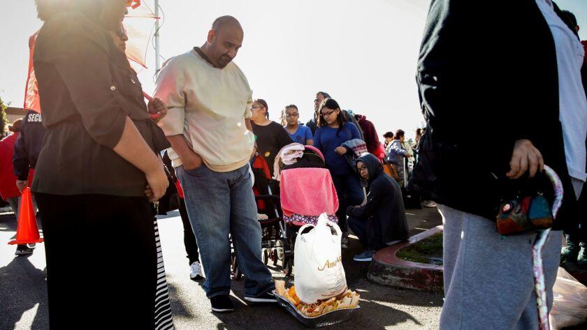 John Cárdenas empuja en el suelo una fuente de tamales en mal estado y una bolsa de masa, mientras espera en fila en Amapola Deli and Market, en Downey, por su reembolso (Jay L. Clendenin / Los Angeles Times).