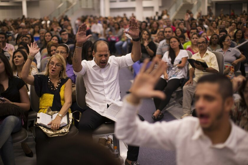 In this Sept. 25, 2014 photo, faithful raise their hands in prayer as they listen to Pentecostal pastor Silas Malafaia's preaching during a service at the Assemblies of God church in Rio de Janeiro, Brazil, Thursday, Sept. 25, 2014. The swelling ranks of Brazil's socially conservative Pentecostal population now represent over one-fifth of the electorate just three decades after barely registering any presence at all. (AP Photo/Leo Correa)