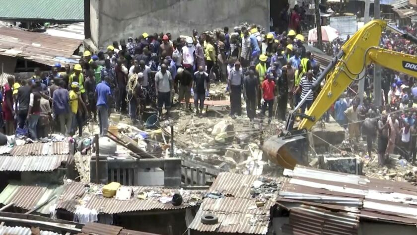 Rescue workers and emergency teams work at the scene of a three-story building that collapsed in Lagos, Nigeria, on March 13, 2019.