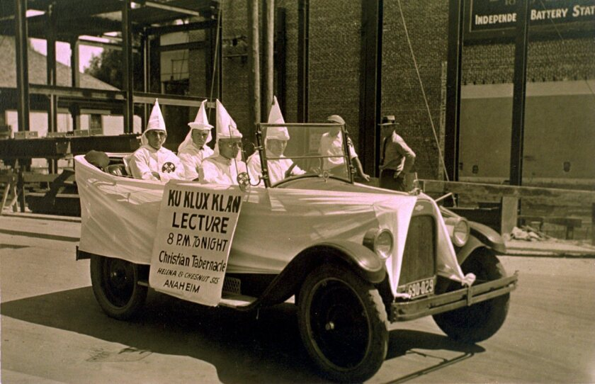 Ku Klux Klan members ride in an automobile advertising a lecture at the Anaheim Christian Tabernacle in 1915.