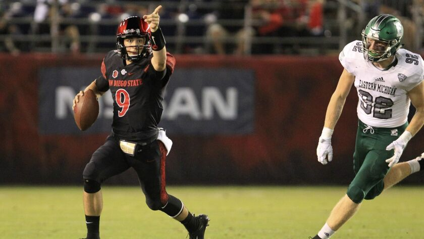Aztecs quarterback Ryan Agnew signals to his receiver as he pursued by Eastern Michigan's Maxx Crosby.