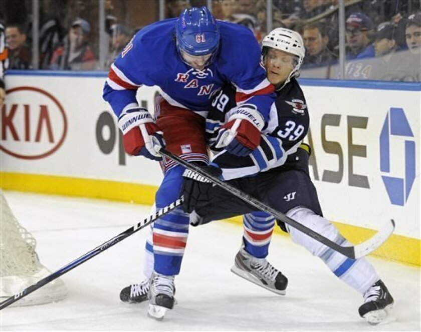 Winnipeg Jets' Tobias Enstrom, right, attempts to slow down New York Rangers' Rick Nash during the first period of an NHL hockey game Monday, April 1, 2013, at Madison Square Garden in New York.  (AP Photo/Bill Kostroun)