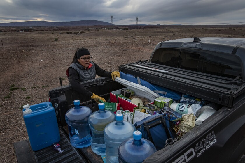 CAMERON, AZ - MARCH 28, 2020: Living without electricity or running water, Navajo Indian Shanna Yazzie unpacks much needed supplies after meeting family members at an exit ramp near Phoenix during the coronavirus pandemic on the Navajo reservation on March 28, 2020 in Cameron, Arizona. She, her two children and elderly mother have been self-quarantining for the past two weeks fearing the virus and had her pantry was bare.(Gina Ferazzi/Los AngelesTimes)