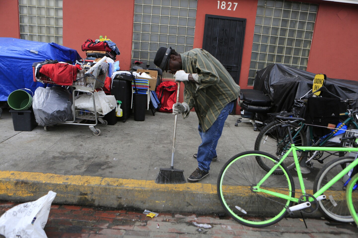 Roy Carter, 57, sweeps the sidewalk where his belongings are gathered on South Hope Street in downtown L.A.