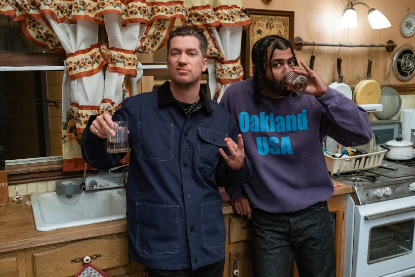 Two men in a kitchen drinking and looking at the camera