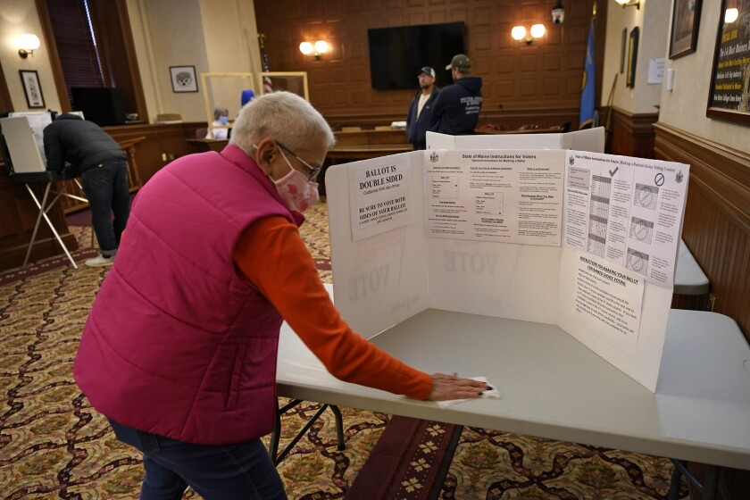 Susan Turcotte, assistant city clerk, disinfects a table after it was used by a resident to fill out an absentee ballot during early voting, Friday, Oct. 30, 2020, in Lewiston, Maine. (AP Photo/Robert F. Bukaty)