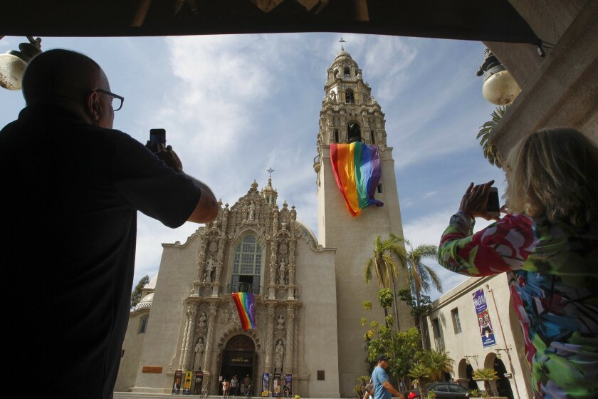 Robert Drake and Debbie Ballard, who work together at the Old Globe Theater, take pictures of the rainbow flags hung from the Museum of Man and the California Tower in Balboa Park in San Diego on Friday. Micah Parzen, Ph.D., CEO of the Museum of Man, said he and his staff decided to put up the fla