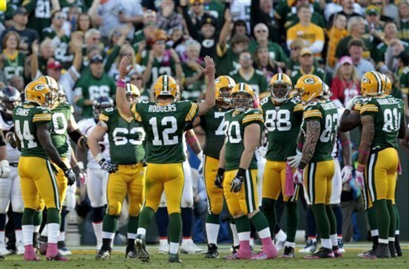 Green Bay Packers quarterback Aaron Rodgers (12) reacts after scoring a touchdown during the second half of an NFL football game against the Denver Broncos, Sunday, Oct. 2, 2011, in Green Bay, Wis. (AP Photo/Mike Roemer)