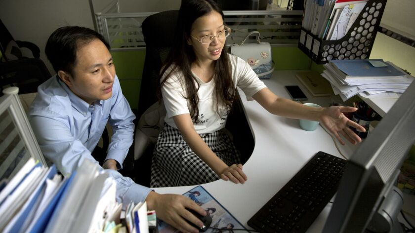 He Jiankui, left, and Zhou Xiaoqin work a computer at a laboratory in Shenzhen in southern China.