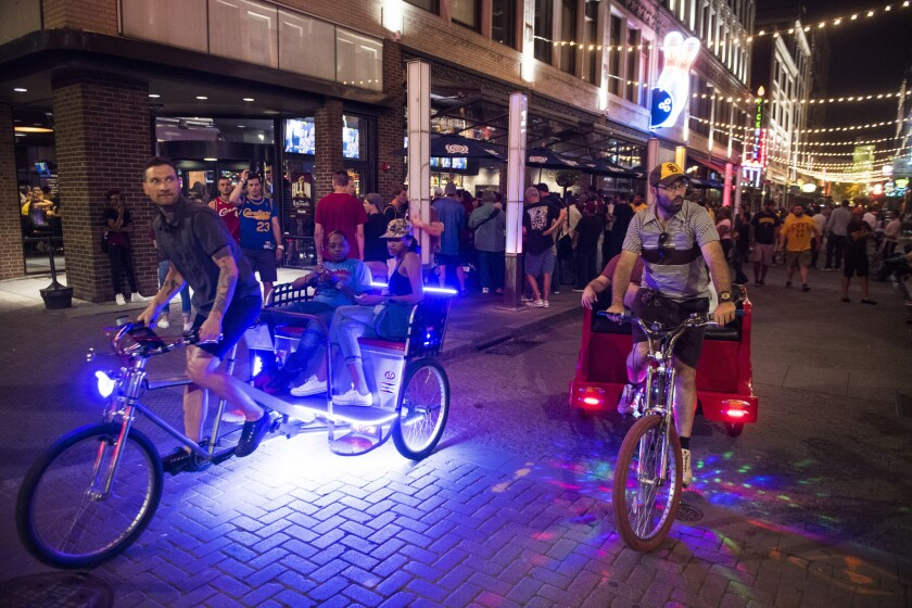 Rickshaws make their way down East 4th Street as fans watch the Cleveland Cavaliers on TVs in the local bars.