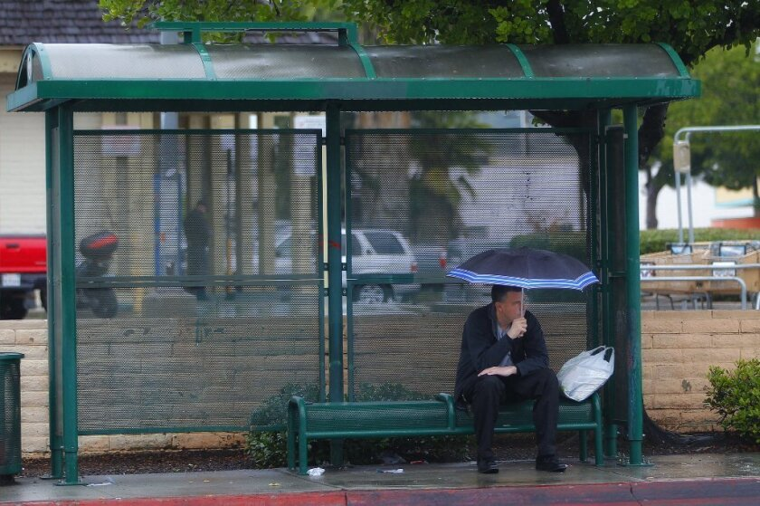 A man tries to stay dry while waiting for the bus at a stop on Broadway Street in El Cajon.