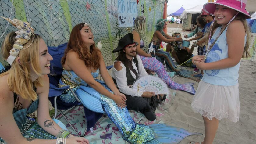 Alexandra MacFreier, 7, gets a kick out of a group of mermaids and pirates from the Ocean Beach Merp