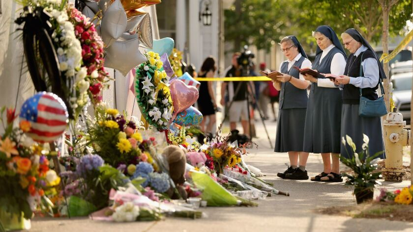 In this June 2015 photo, sisters of the Order of the Daughters of St. Paul pray outside the historic Emanuel African Methodist Episcopal Church in Charleston, South Carolina, where self-proclaimed white supremacist Dylann Roof killed nine people during a prayer meeting.