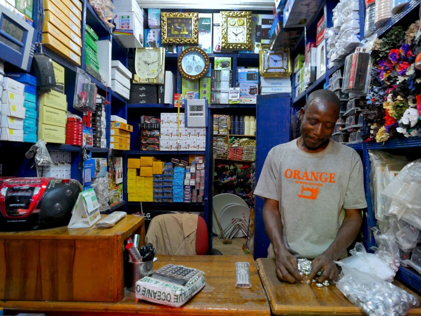 Adama Keita's colleague counts buttons in his shop in Dabanani market in central Bamako, Mali on Mar