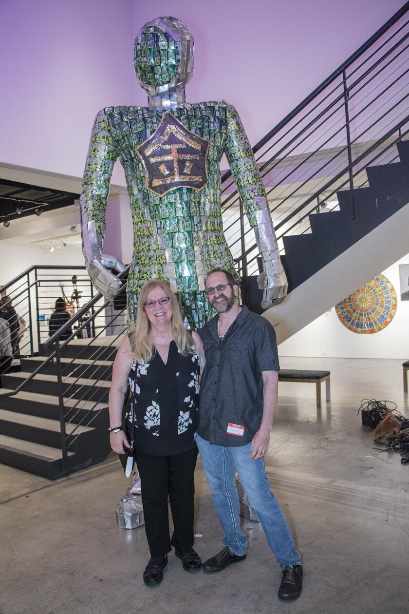 San Diego Art Prize winners Debby and Larry Kline, with their supersized 'Alchemist,' made out of Perrier cans.