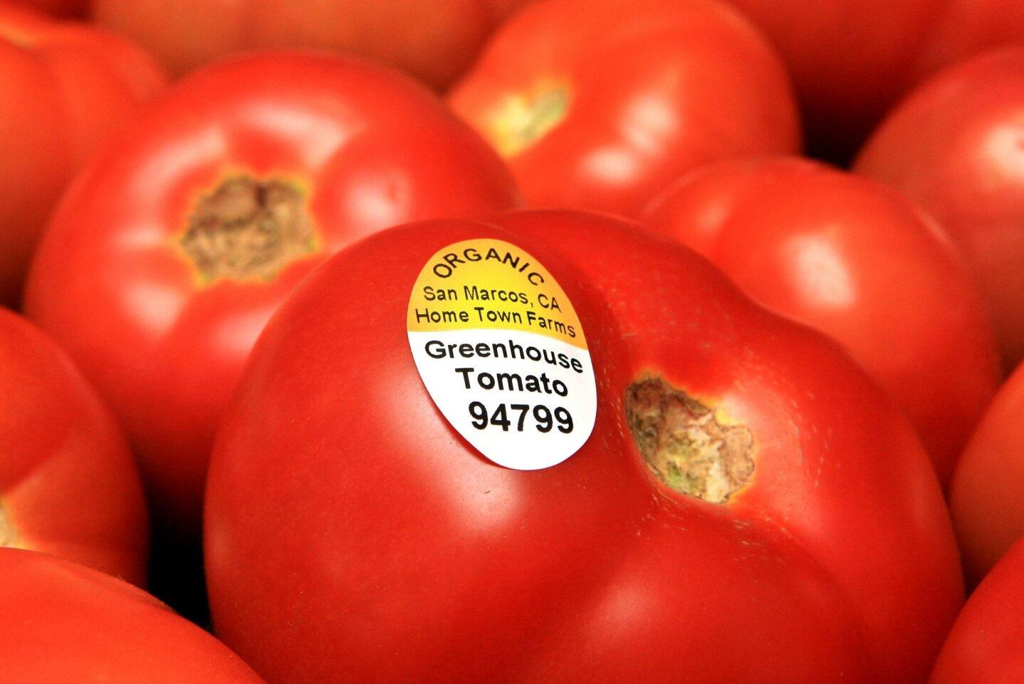 """At Home Town Farms a label signifying """"organic"""" is displayed on a a tomato on display for sale."""