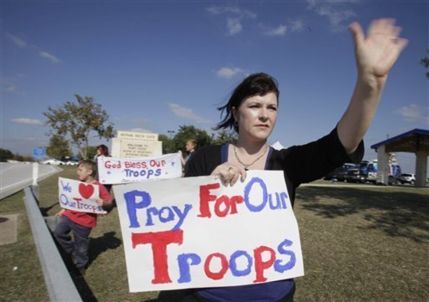 Kendra Thomas, of Waco, Texas, waves to people driving into the front gate of the Army base at Fort Hood, Texas on Saturday, Nov. 7, 2009. (AP Photo/LM Otero)