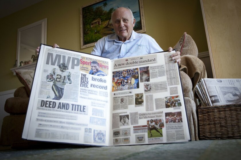 Dave Mirisch shows one of the scrapbooks he uses to chronicle major sporting events.