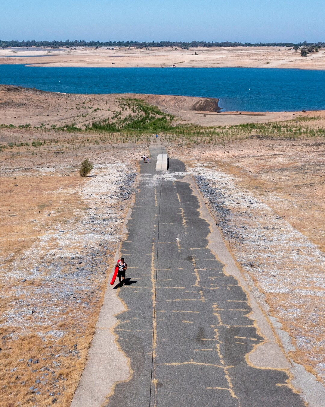 A kayaker carries his kayak hundreds of feet up a ramp from the lakeshore to a parking area at Folsom Lake.