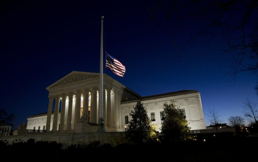 An American flag flies at half-staff in front of the U.S. Supreme Court building in honor of Supreme Court Justice Antonin Scalia as the sun rises in Washington, Sunday, Feb. 14, 2016. Scalia, the influential conservative and most provocative member of the Supreme Court, has died. He was 79. (AP Ph