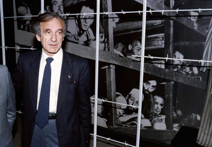 Nobel Peace Prize laureate and writer Elie Wiesel at the Yad Vashem Holocaust memorial in Jerusalem in 1986. The image behind shows him, bottom, third from right, and other inmates at the Nazis' Buchenwald concentration camp.