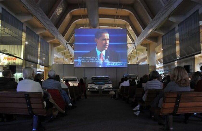 People gather in a mock drive-in theater to watch and listen to the inauguration speech of newly sworn-in President Barack Obama on a large screen televisions at the Henry Ford Museum, Monday, Jan. 20, 2009 in Dearborn, Mich. The museum held an event where people could come watch the presidential i