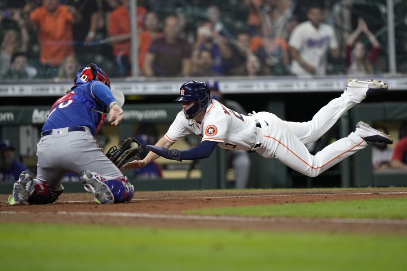 Houston Astros' Chas McCormick (20) is tagged out at home plate by Texas Rangers catcher Jose Trevino (23) during the 10th inning of a baseball game Thursday, May 13, 2021, in Houston. (AP Photo/David J. Phillip)