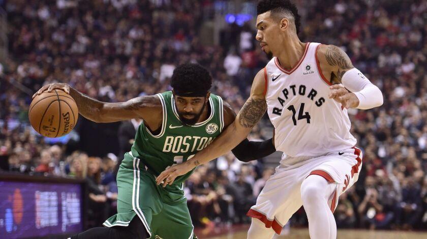 Boston Celtics guard Kyrie Irving (11) controls the ball as Toronto Raptors guard Danny Green (14) d