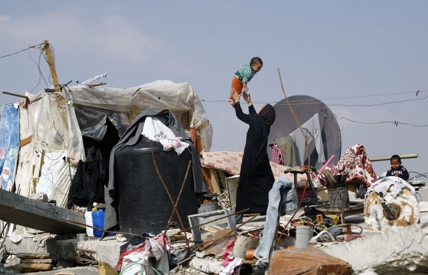 A Palestinian woman plays with her child on the rubble of their family's home, which was destroyed during the 50-day war between Israel and Hamas in the Gaza Strip.