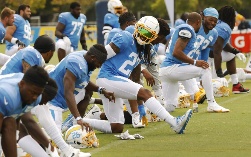 Chargers players stretch during training camp in Costa Mesa on Monday.