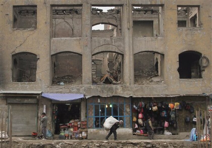 An Afghan street vendor passes a building, damaged during the 1990s civil war, as he carries a sack containing used clothes to sell in Kabul, Afghanistan, Monday, April 2, 2012. (AP Photo/Musadeq Sadeq)