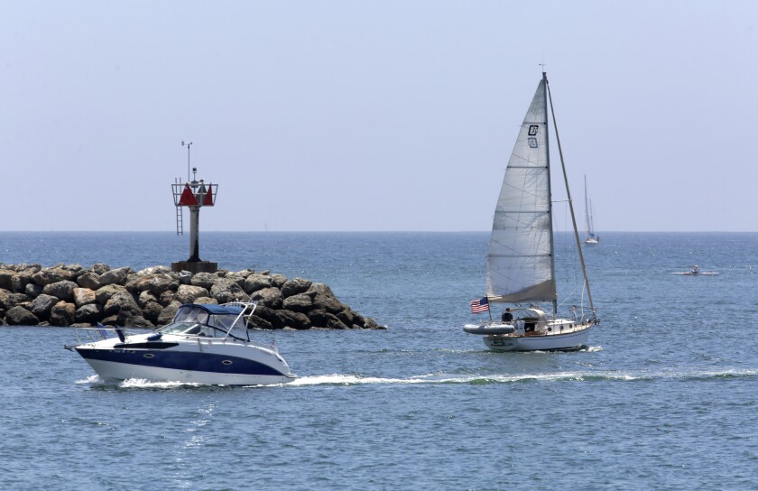 Boats cruise in and out of Oceanside Harbor on Friday.