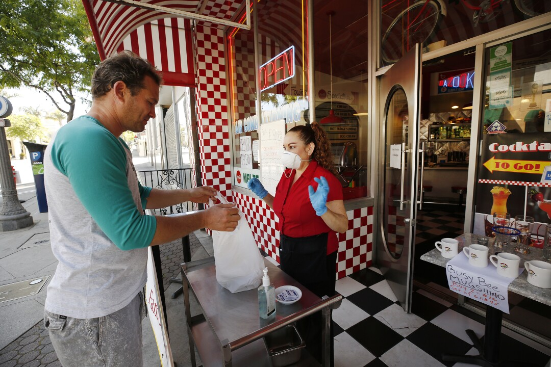 Yoeli Barag buys breakfast from Nora Nancy at Busy Bee Diner in Ventura on Wednesday.