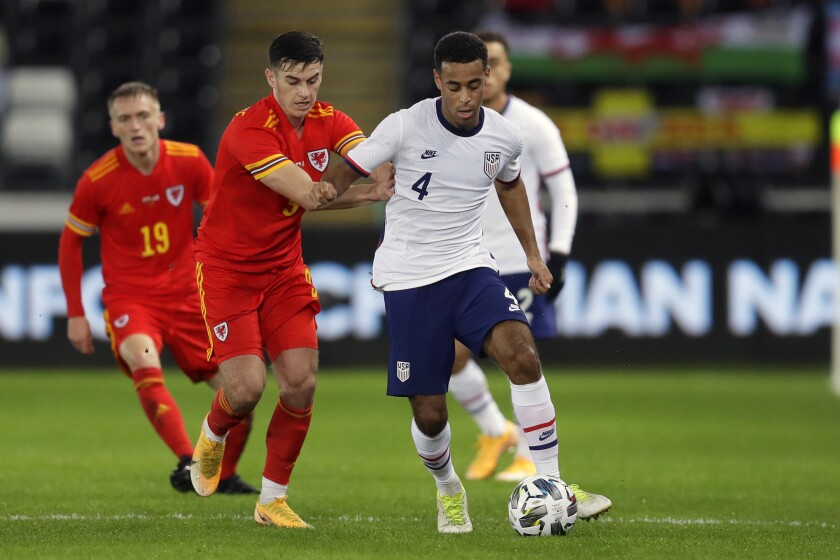 United States' Tyler Adams controls the ball as Wales' Tom Lawrence holds him during the international friendly.