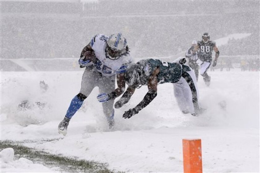 The Detroit Lions' Joique Bell, left, is tackled by Philadelphia Eagles' Bradley Fletcher during the first half of a snowy NFL football game in Philadelphia.