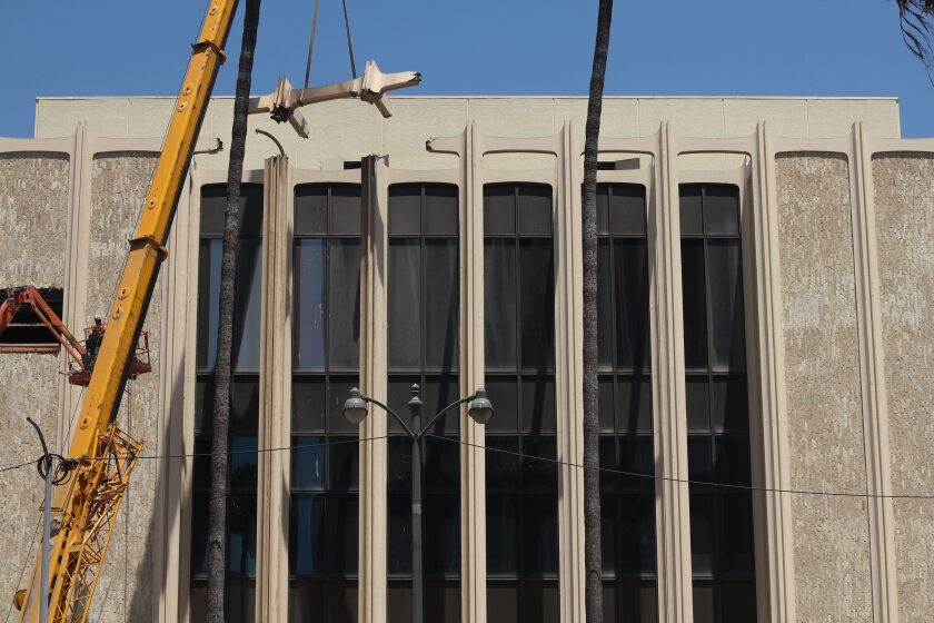 A massive construction crane is seen removing a fragment of LACMA's columnar façade.