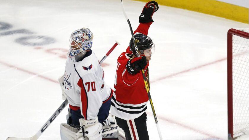 Chicago Blackhawks left wing Alex DeBrincat (12) celebrates after scoring a goal past Washington Cap