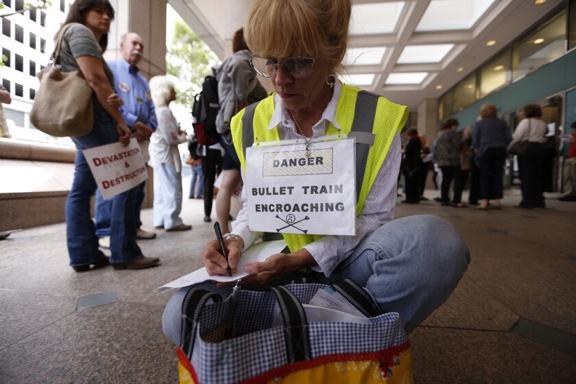 Shannon McGinnis from Kagel Canyon joins opponents of the current route for a high speed rail before they converge on a meeting of the California High-Speed Rail Authority in downtown Los Angeles.