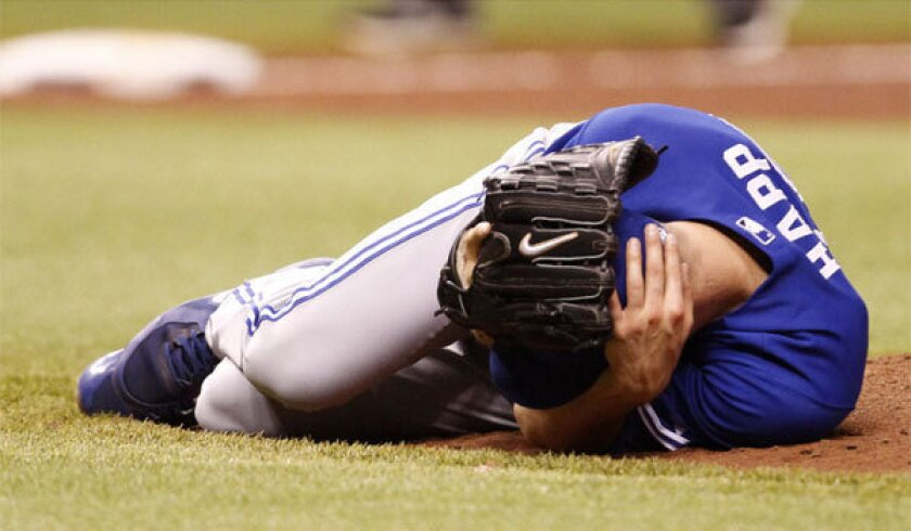 Toronto pitcher J.A. Happ lies on the field after he was hit in the face by a line drive during the second inning of the Blue Jays' 6-4 victory over Tampa Bay.